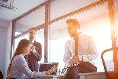 Succesfull business people studying documents in sunny office. Male And Female Colleagues Exchanging Ideas In Sunny Boardroom About New Project. Business Concept royalty free stock photos