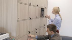 Male and female colleagues are opening wooden lockers in the office. Blond businesslady in blue shirt is coming, getting her black leather bag from the box and stock video