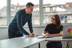 Colleagues smiling at each other in the office while working. Male and female colleagues smiling at each other in the office while working stock photos