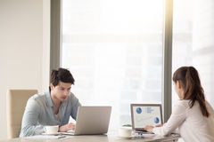 Male and female colleagues working at office table using laptops royalty free stock images