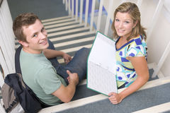 Male and female college students sitting on stairs.  Stock Images