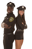 Male and female cop back to back smiling Royalty Free Stock Photography