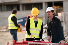 Male and female coworkers on construction site. Construction manager checking projects on construction site with a female engineer wearing safety jacket and stock images