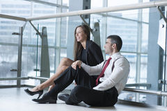 Male and female coworkers sitting and joking together Royalty Free Stock Photo