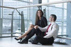 Male and female coworkers sitting and joking together Royalty Free Stock Images