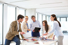 Male and female design professionals having discussion at table in new office Royalty Free Stock Photo