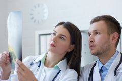 Male and female doctors discussing x-ray image. Doctors discussing new way of treatment. stock photos