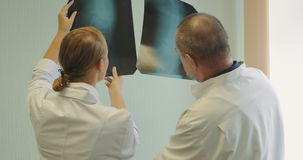Male and female doctors examining x-ray images. Back shot of man and woman doctors examining, discussing and comparing two knee x-rays images stock video