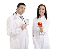 Male and female doctors holding apple and pills - Stock Image Royalty Free Stock Photos