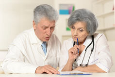 Male and female doctors. Portrait of a male and female doctors discussing diagnosis Royalty Free Stock Photos
