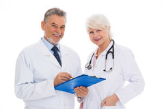 Male and female doctors. Portrait of male and female doctors standing over white background Royalty Free Stock Photo