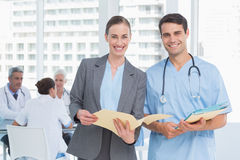 Male and female doctors with reports Royalty Free Stock Photos