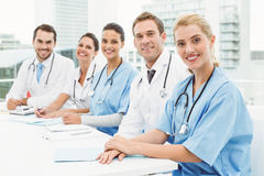 Male and female doctors sitting in row Stock Photo