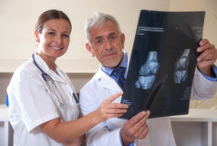 Male and female doctors smiling examining x-ray te Royalty Free Stock Image