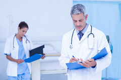 Male and female doctors working on reports Royalty Free Stock Photo