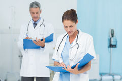 Male and female doctors working on reports Royalty Free Stock Image