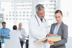 Male and female doctors working on reports Stock Photo