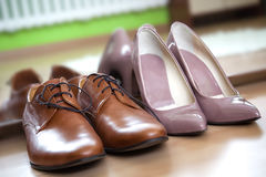 Male and female dress shoes. Close up photo of pink latent pointy female heels and male leather camel brown lace up dress shoes, placed against mirror on the royalty free stock photography