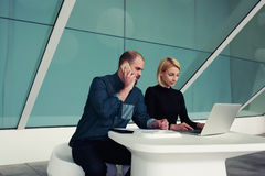 Male and female economists using cell telephone and laptop computer while working together in office. Young businessman talking on mobile phone with client while stock images