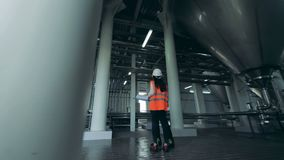 A male and a female engineers are having a conversation in brewery unit stock video footage
