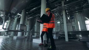 A male and a female engineers are observing a distillery facility stock footage