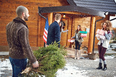 Male and female on entrance of mountain house. Male and female with Christmas gifts and tree on entrance of mountain house Royalty Free Stock Images