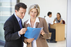 Male And Female Executive Discussing Report With Office Meeting In Background royalty free stock photo