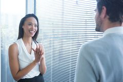 Male and female executives interacting with each other near window. In office Stock Photography