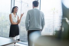 Male and female executives interacting with each other near window. In office Stock Photo