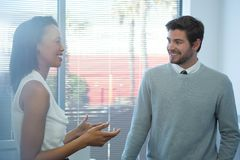 Male and female executives interacting with each other near window. In office Stock Image