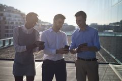 Male and female executives using digital and mobile phone stock photography