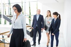 Executives Walking On Corridor In Office. Male and female executives walking on corridor in office royalty free stock photography