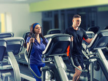 Male and female exercising on the crosstrainer machines. In fitness center Stock Photo