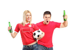 Male and female fans holding beers and football Stock Photos