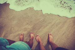 Male and female feet couple are standing on the sandy beach. Honeymoon concept. vintage color tone style Stock Image
