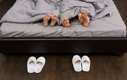 Male and female feet, man`s hand scratching his feet under grey. Blanket in modern stylish bed near two pairs of white slippers Royalty Free Stock Photo