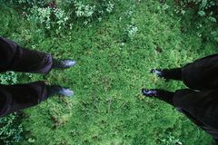 Male and female feet in rubber boots in thick moss.  Royalty Free Stock Photography