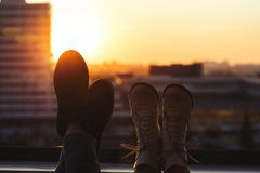 Male and female feet in shoes on the balcony. City and sunset background Royalty Free Stock Image
