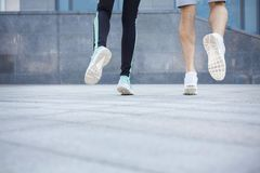 Closeup of male and female feet running, back view. Male and female feet in sneakers. Couple running, crop, back view, copy space. Fitness, sport, foot wear and Royalty Free Stock Image