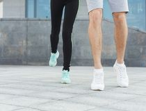 Closeup of male and female feet running. Male and female feet in sneakers. Couple running, crop, copy space. Fitness, sport, foot wear and healthy lifestyle Stock Images