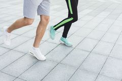 Closeup of male and female feet running, side view. Male and female feet in sneakers. Couple running, crop, copy space. Fitness, sport, foot wear and healthy Stock Photos