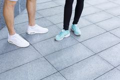 Closeup of male and female feet running. Male and female feet in sneakers. Couple standing, having rest after running, crop, copy space. Fitness, sport, foot Stock Photo