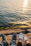 Male and female feet in sneakers on the rocky shore with beautiful view on wavy water, friendship or love concept. Trust. Male and female feet in sneakers on the Royalty Free Stock Photos