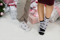 Male and female feet of socks with patterns of penguins and snowflakes stand one stop on the other. Male and female feet of socks with patterns of penguins and Royalty Free Stock Image