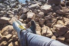 Male and female feet  lay on coastal stones. Male and female feet in sporty shoes lay on coastal rough stones. Family travel lifestyle background Royalty Free Stock Photos