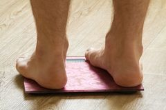 Male feet standing on the scale. Male of female feet standing on the scale, closeup royalty free stock photo