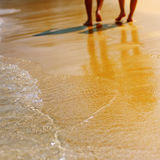 Male and female feet walk on the sandy beach Stock Photo