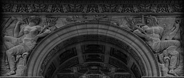 Male and female figures on the arch. Shot in black and white detail of the sculpture on the facade of this historic building representing some characters / stock photos