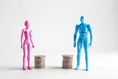 Male and female figurines standing next to equal piles of coins. Royalty Free Stock Photography