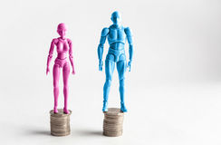Male and female figurines standing next to equal piles of coins. Stock Photos